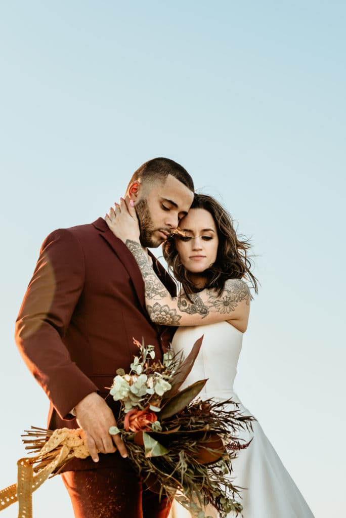 Madly in love elopement couple embrace during their Bohemian wedding