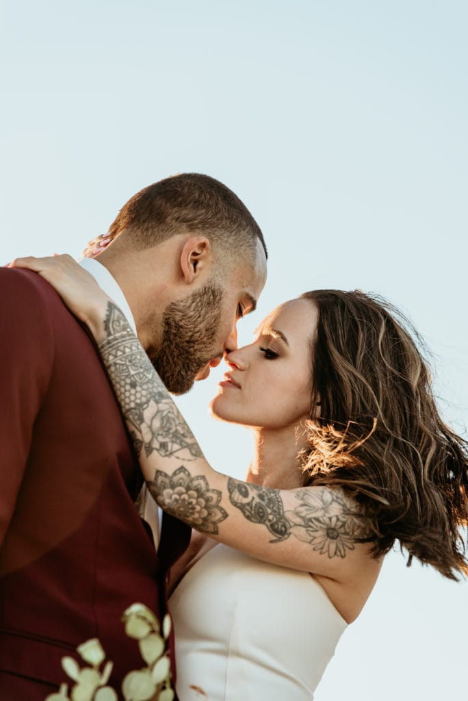 Bride and groom embrace, showing her intricate tattoo sleeve