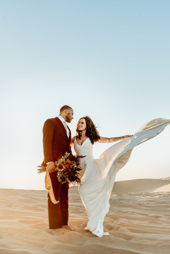 Bride spins her flowing white dress into the sweeping desert wind during their sunset wedding at Glamis Sand Dunes