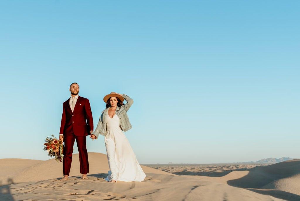 Bride in boho denim jacket and brimmed hat, groom in dark maroon suit, both barefoot standing on top of sea of sand
