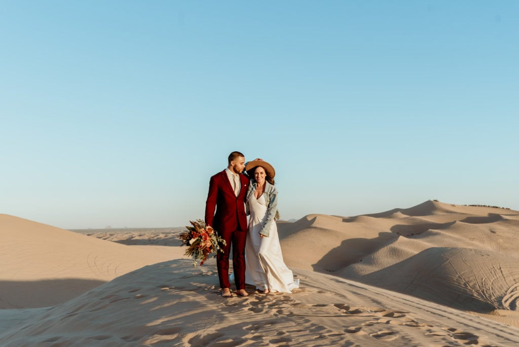 Happy elopement couple standing on a mountain of sand during the sunset