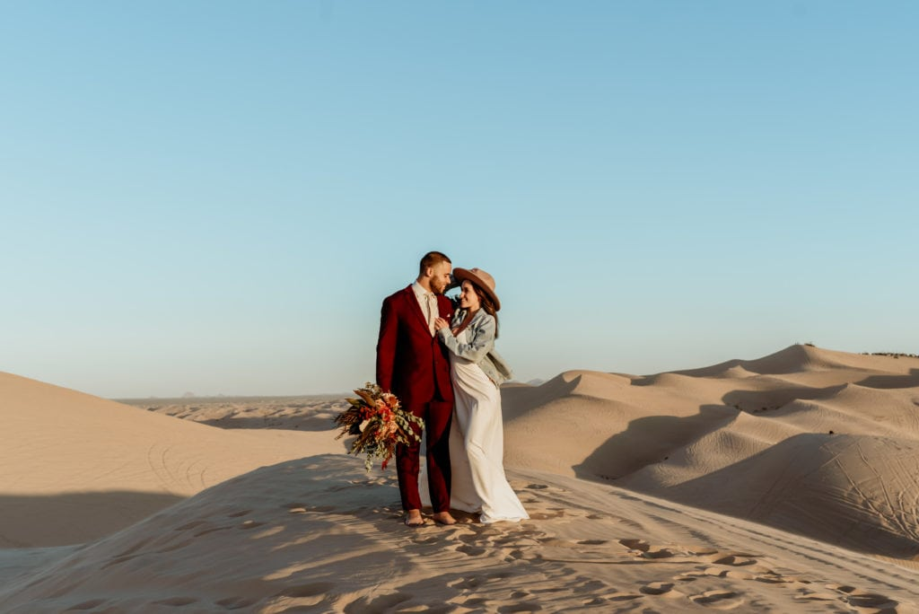Bride holds her hat to keep it from blowing away while embracing her husband on top of waves of golden sand