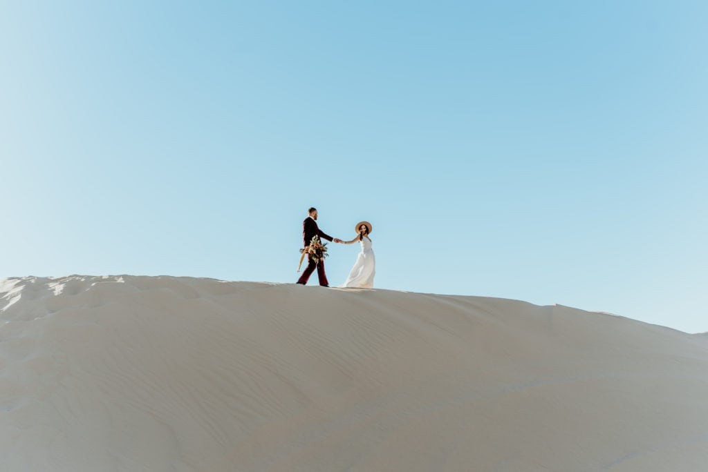 Groom carrying bouquet as bride leads him across the sand during their minimalistic desert elopement