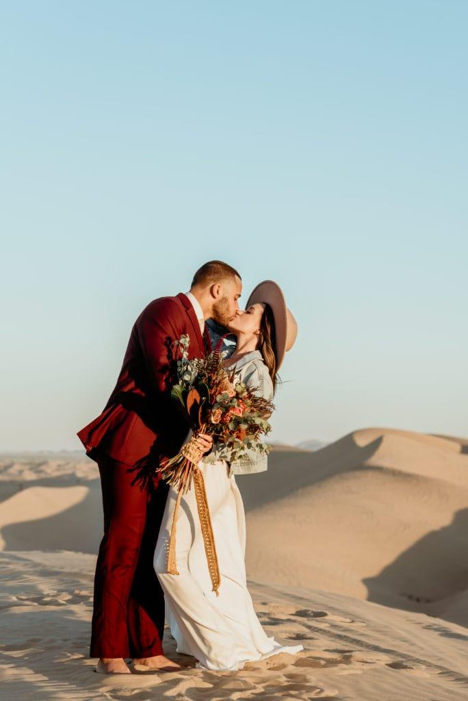 Romantic kiss with a dip during boho desert elopement