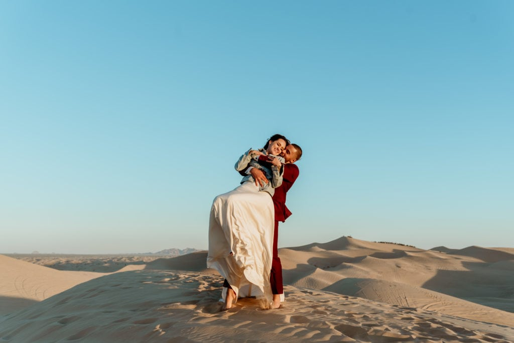 Groom swinging and spinning his wife on top of sand peaks at Glamis Sand Dunes