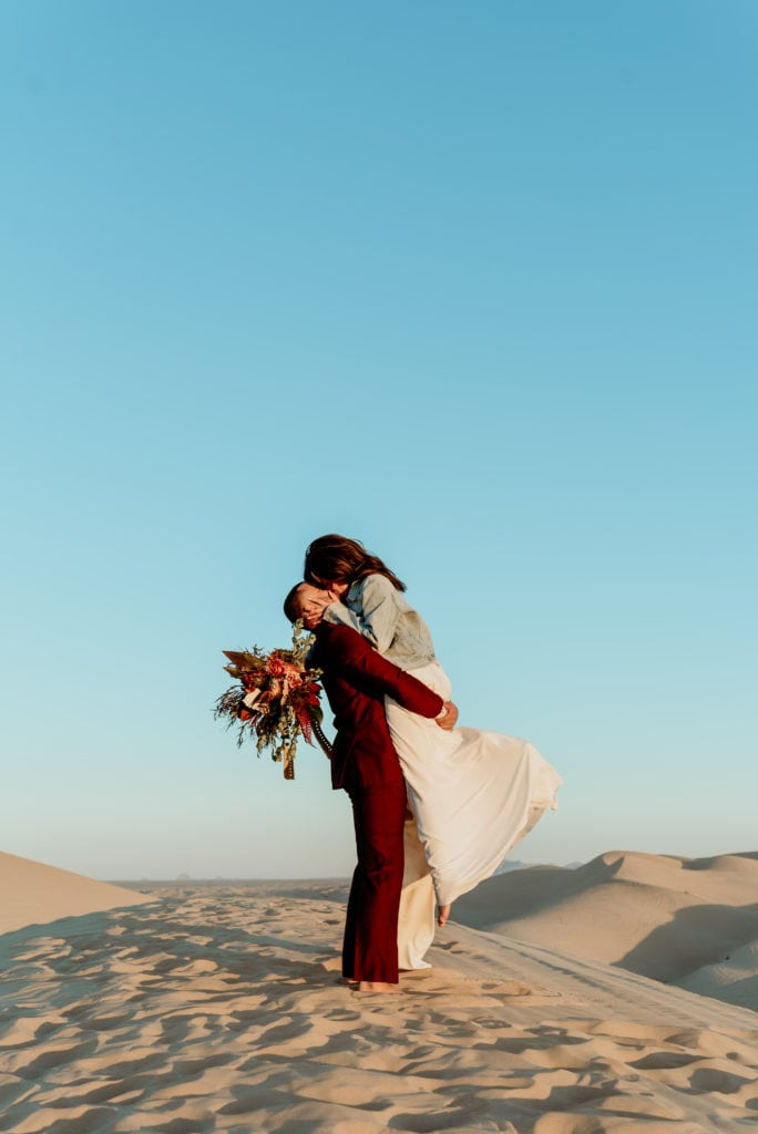 Groom lifting bride in the air during a romantic kiss in the desert