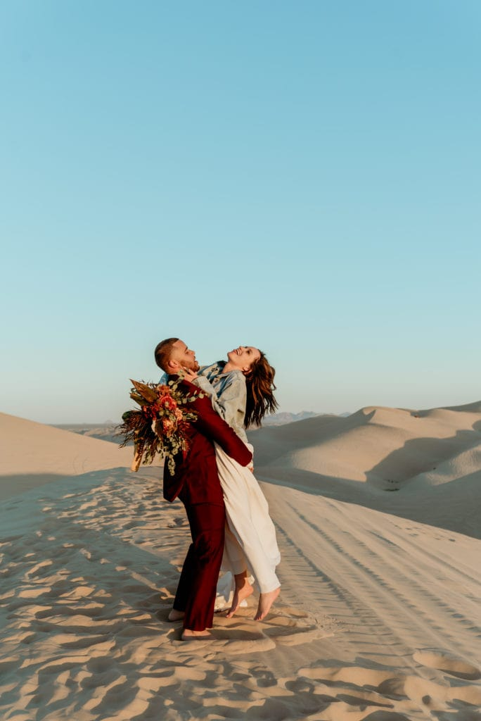 Groom spins his barefoot wife during their Glamis Sand Dune elopement