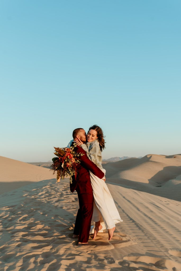 Waves of golden sand as far as the eyes can see behind flirtatious boho wedding couple