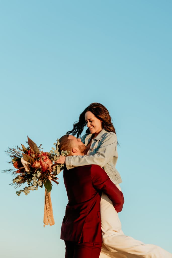 Bride smiling down on groom with her deep, vibrant bouquet as he lifts her into the sunset