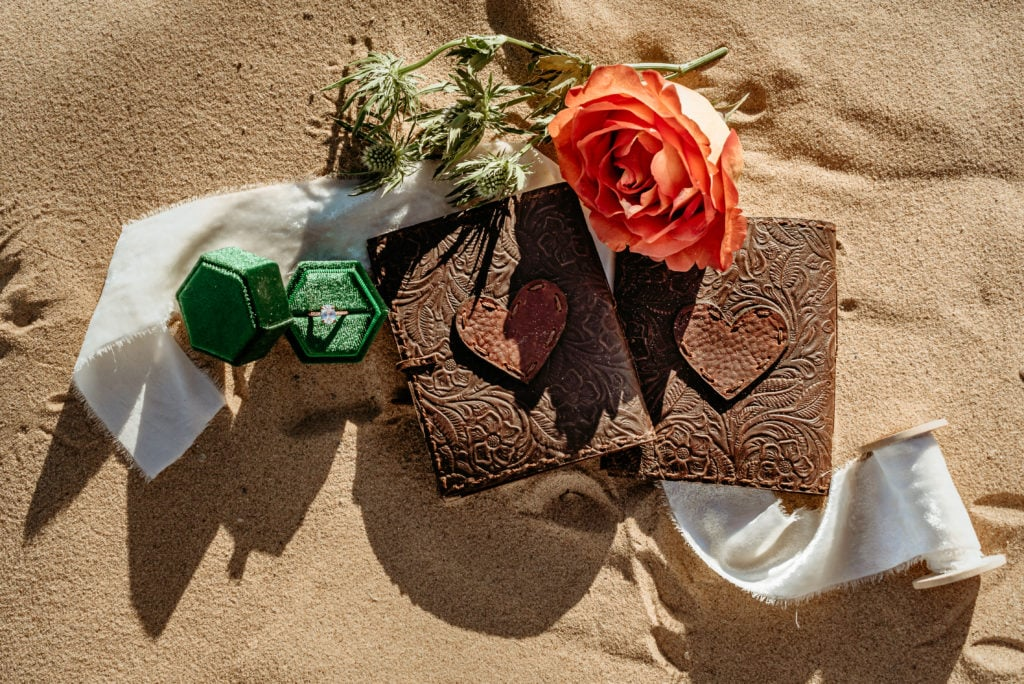 Leather embossed vow books, a deep orange rose, and vibrant ring box show details from this Glamis Elopement