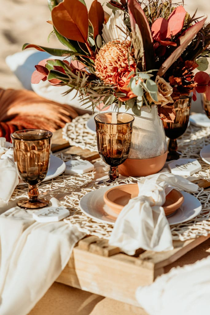 Earthy terracotta details in this boho chic picnic elopement setup