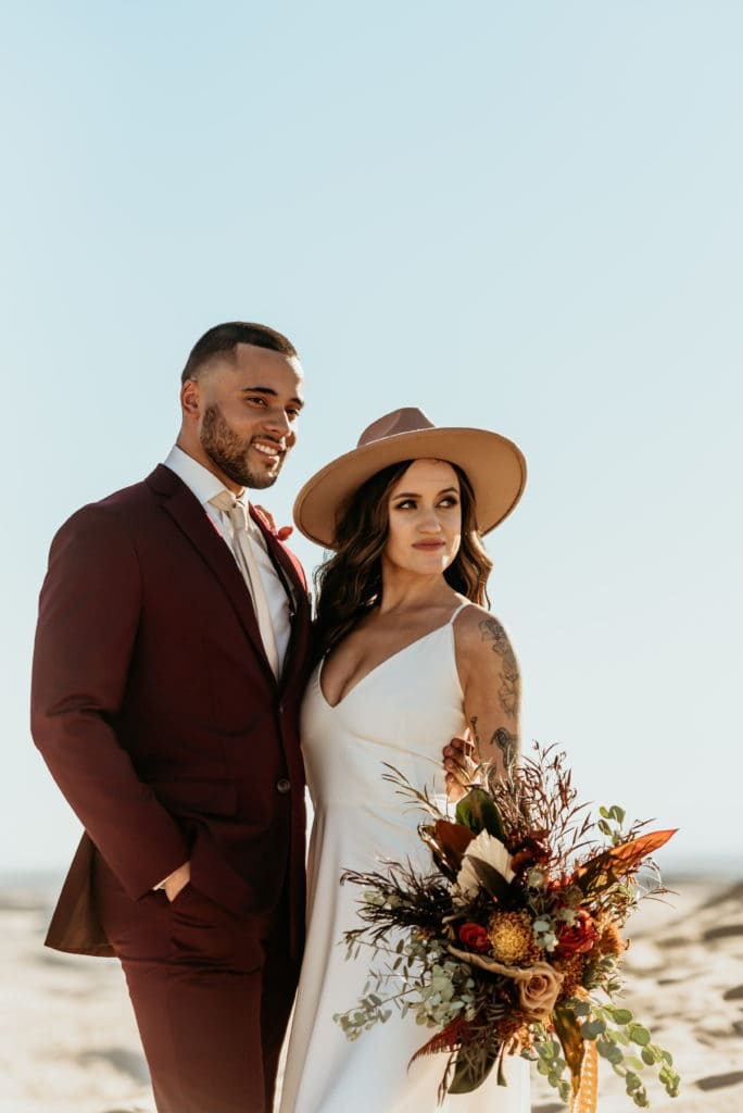 Bride in her boho hat and wildflower bouquet with her husband in a dark red suit at Glamis Sand Dune elopement