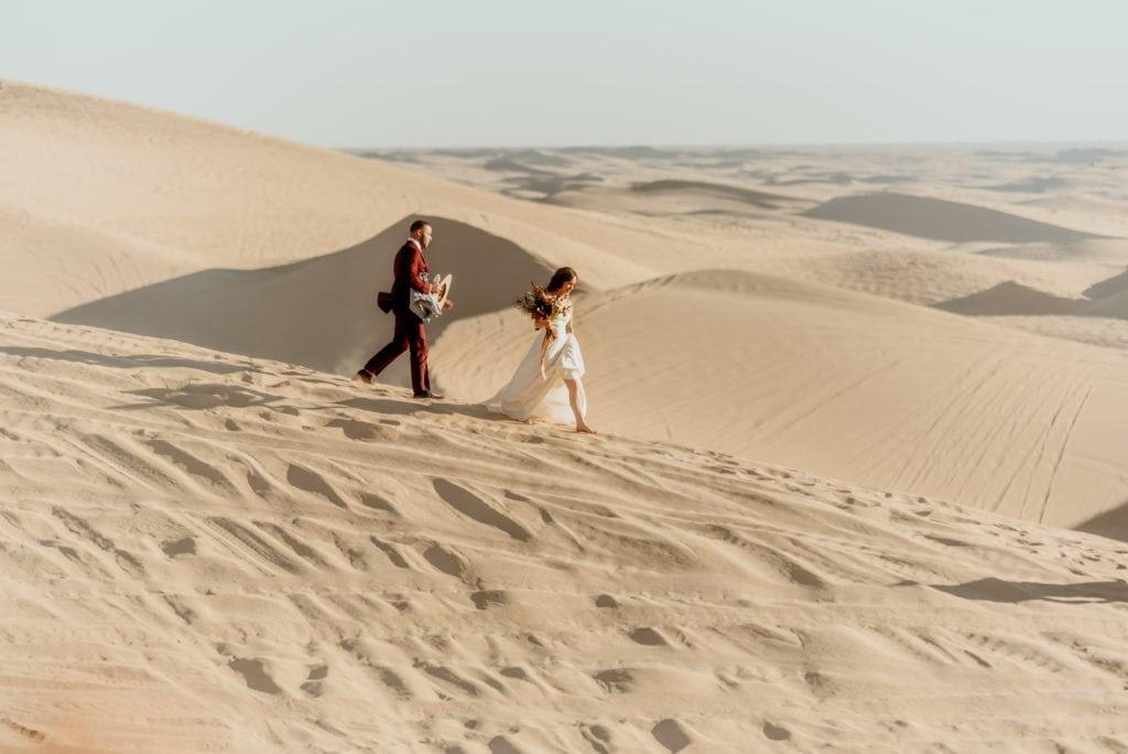 Barefoot couple treks across the barren desert during their Imperial Sand Dune elopmeent