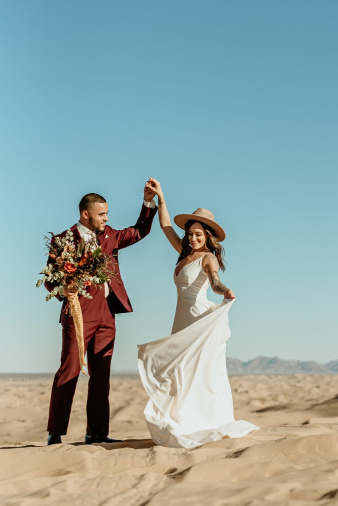 Groom in maroon tux spins his bride in a long minimalist white dress and boho hat