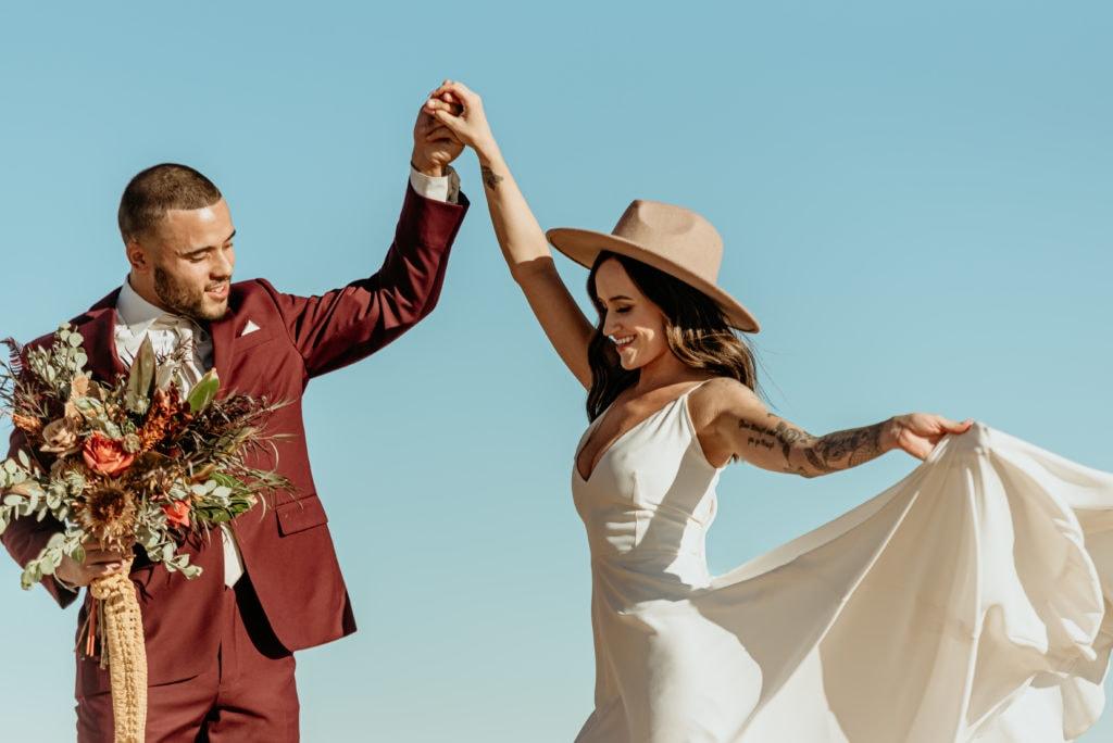 Bride and groom dance in the desert sun