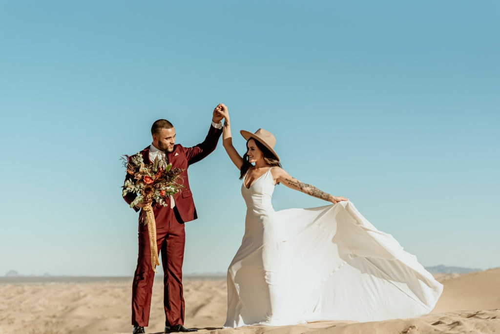 Elopement couple dancing as the bride's dress flows in the wind sweeping across the Imperial Sand Dunes