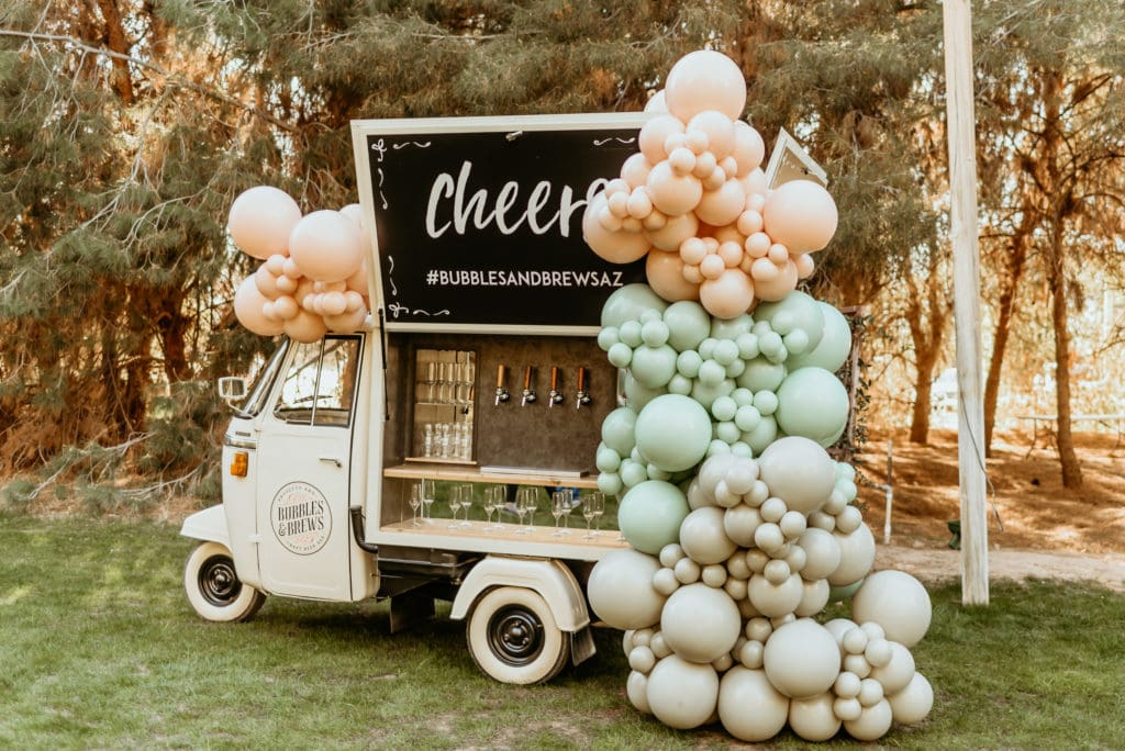 Bubbles and brews traveling bar decorated with cascading balloons