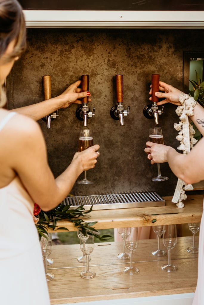 guests pouring beer into their flasks from the Bubbles and Brews vintage bar