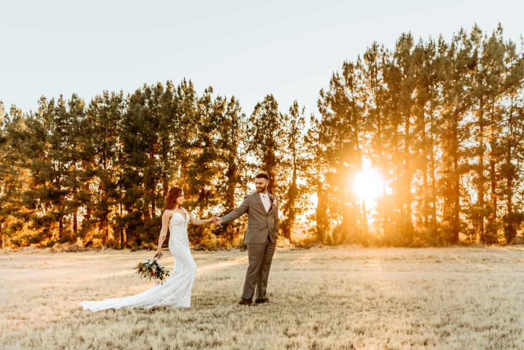 Groom leads bride through the field at sunset