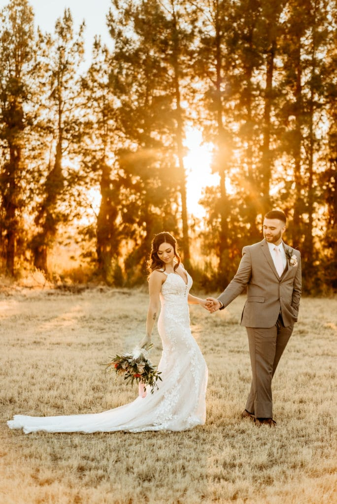 Wedding couple walking through tree lined field during sunset