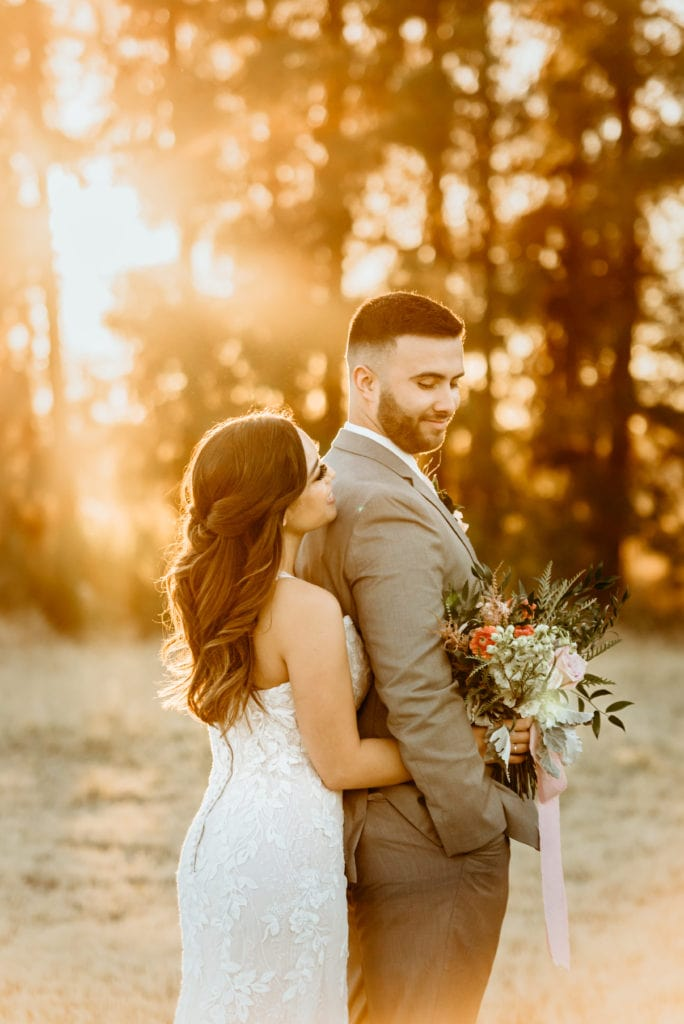 Sun rays shine through on wedding couple at Schnepf Farm wedding in the meadow