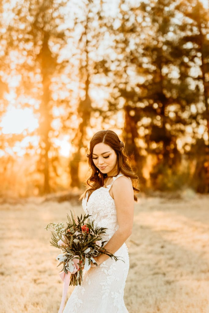 Bride looking down at her bouquet surrounded by sunset glow