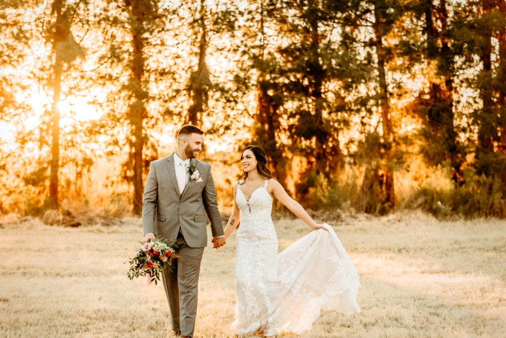Bride and groom walking hand in hand while golden rays shine through a wall of evergreens