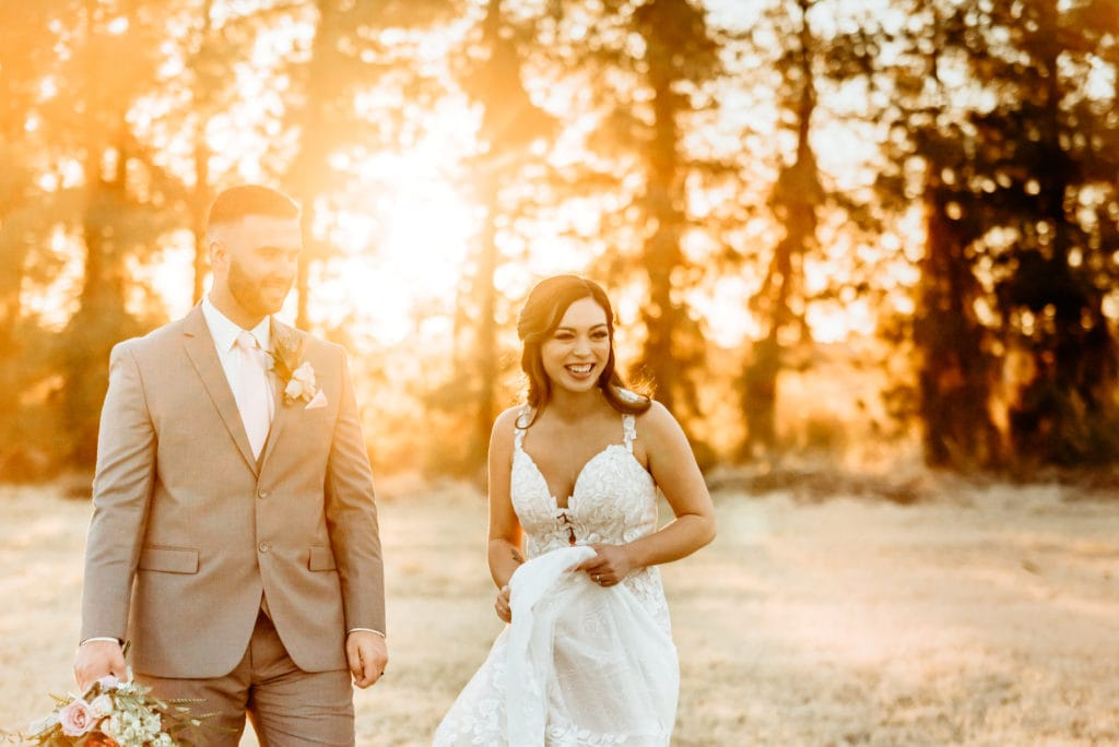 Couple laughing during Schnepf Farms wedding in the meadow