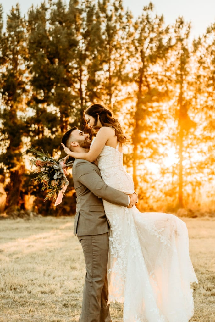 Groom lifts bride during golden hour sunset glow