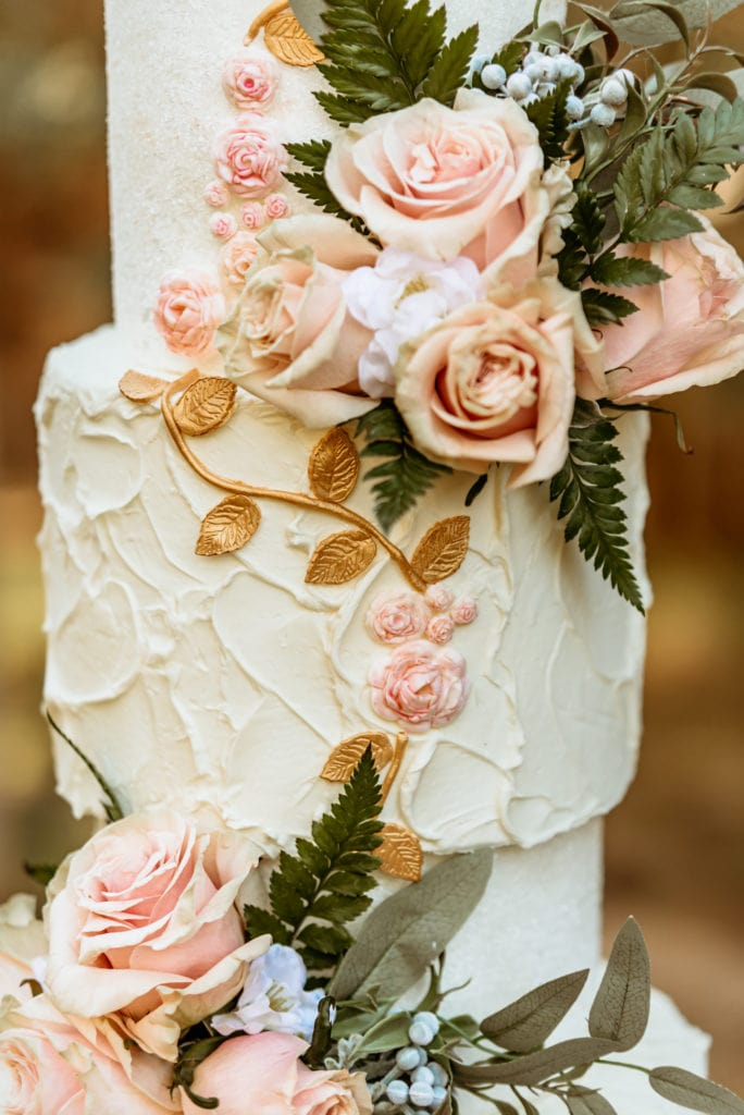 Intricate pink roses and golden leaves on 3 tiered wedding cake