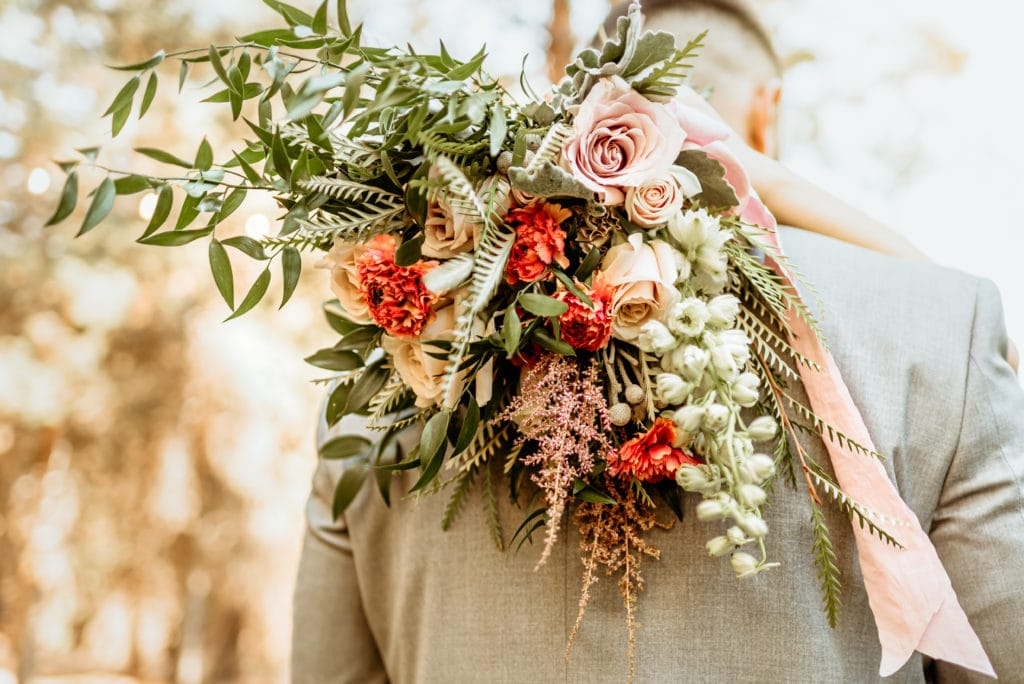 Wild and free wedding bouquet with reds, pinks, and cream florals