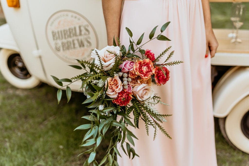 Bridesmaid's bouquet with vibrant pinks and strands of green