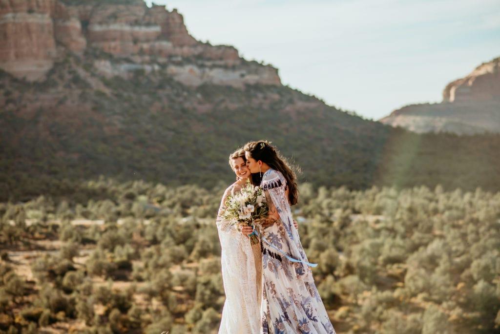 Brides embrace as the warm sun glow surrounds them