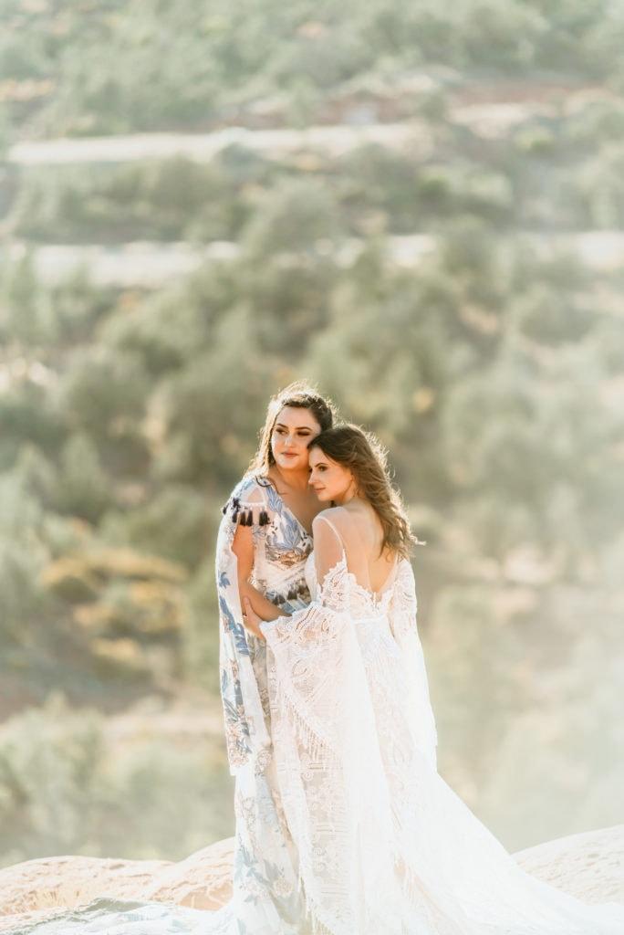 Warm light surrounds brides in romantic embrace