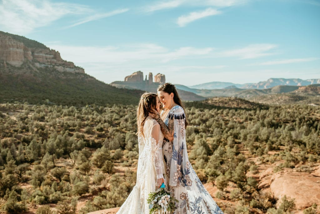Brides embrace with views of Cathedral Rock in the distance wearing Rue De Seine Dresses