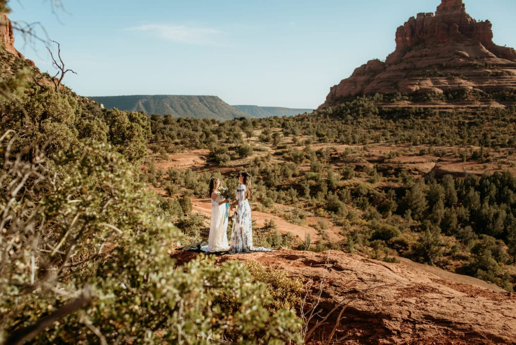 View of Bell rock as two brides say their elopement vows in Sedona, Arizona