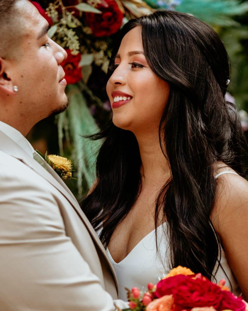 Beautiful Latina bride gazing at her groom