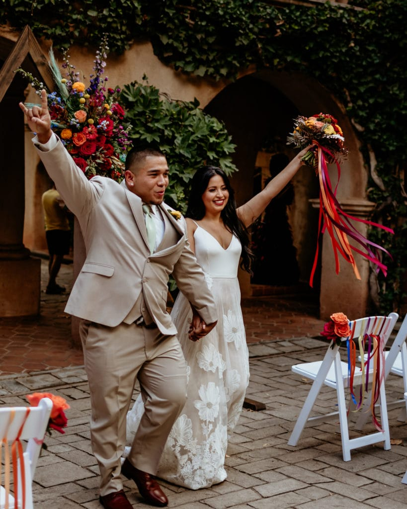 Bride and groom celebrating as they come down the isle