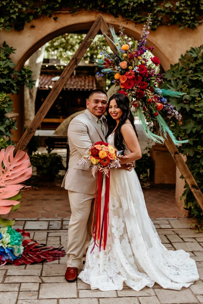 Bide and groom in front of wedding arch decorated with vibrant flowers