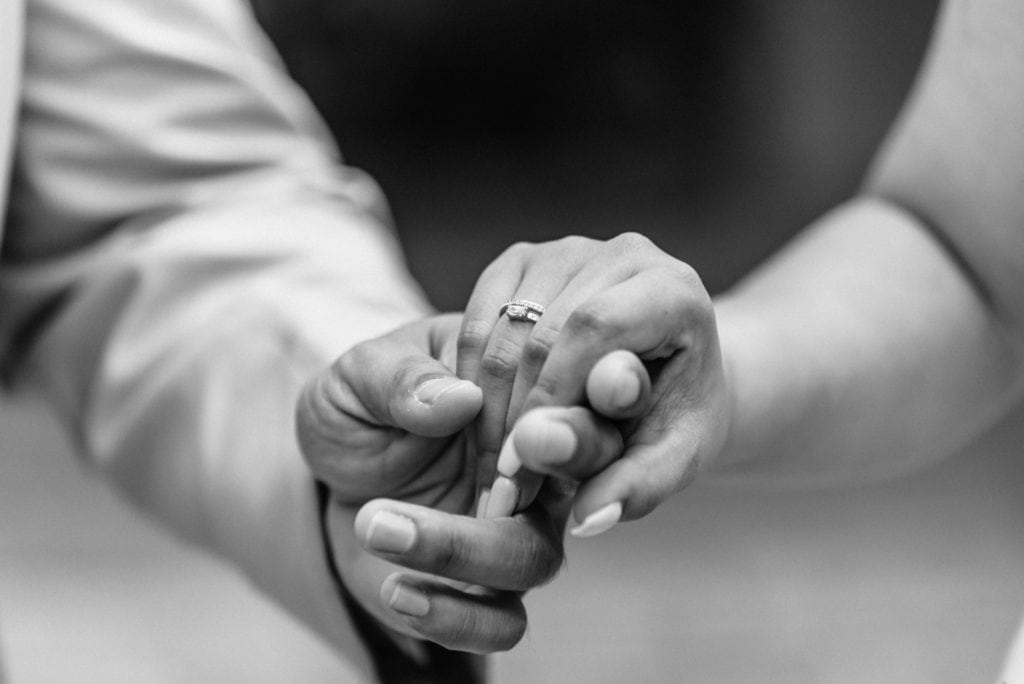 Detail shot of bride and groom holding hands