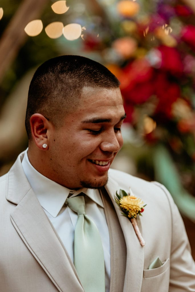 Groom in tan suit with yellow boutonniere