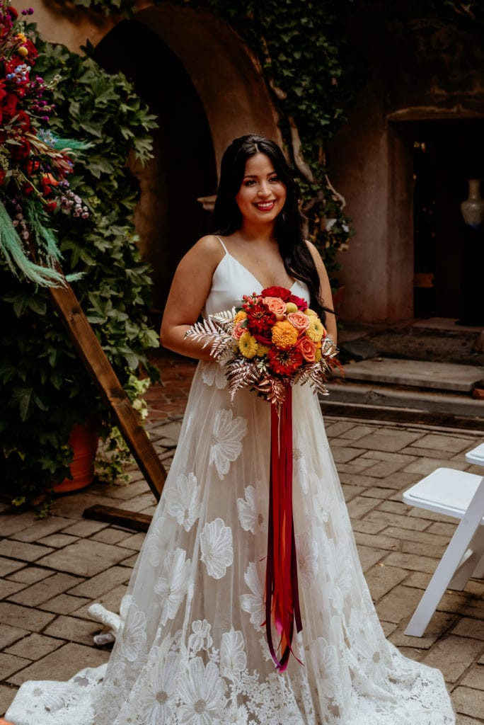 Bride in long floral lace dress holding bouquet with yellows, reds, orange and gold touches