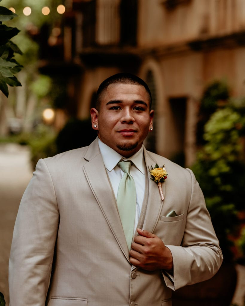 Groom in tan suit, mint tie, and yellow boutonniere