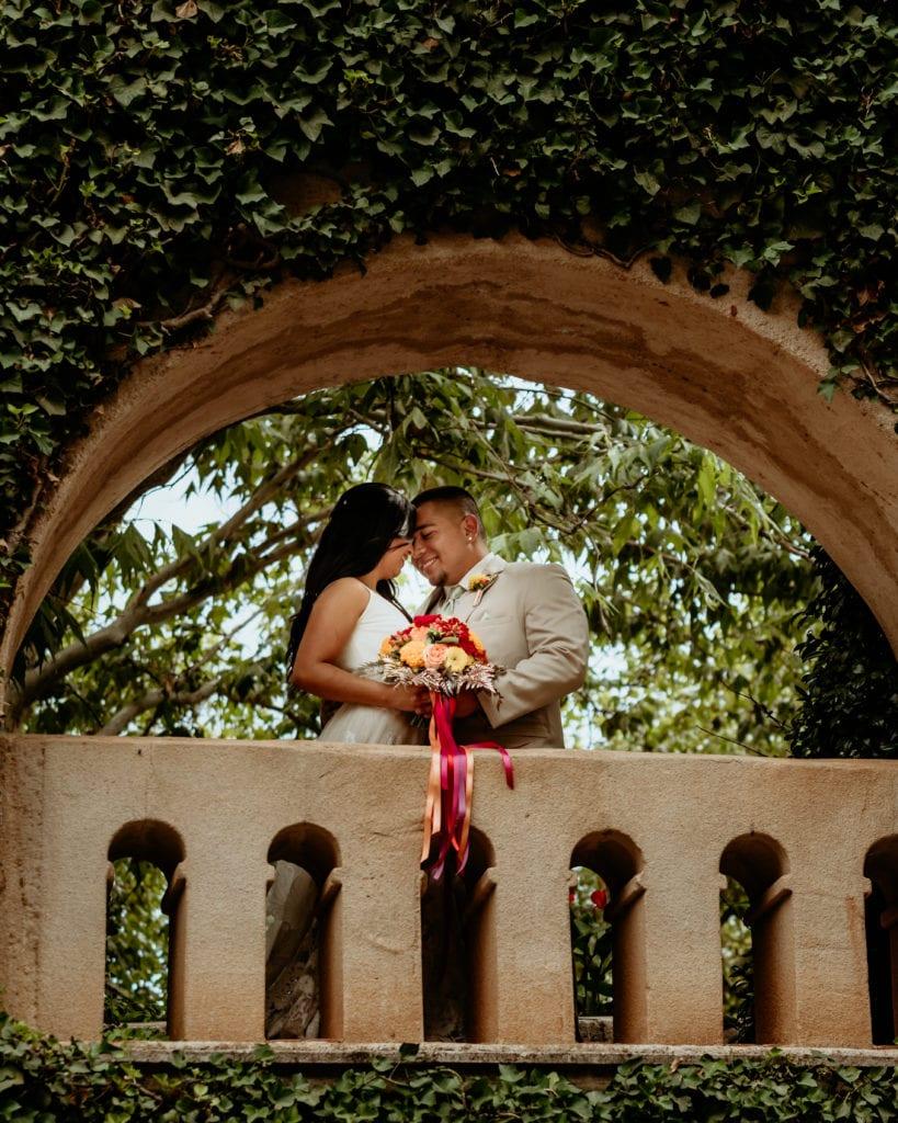 Couple embracing through the vined balcony at Tlaquepaque Art Center