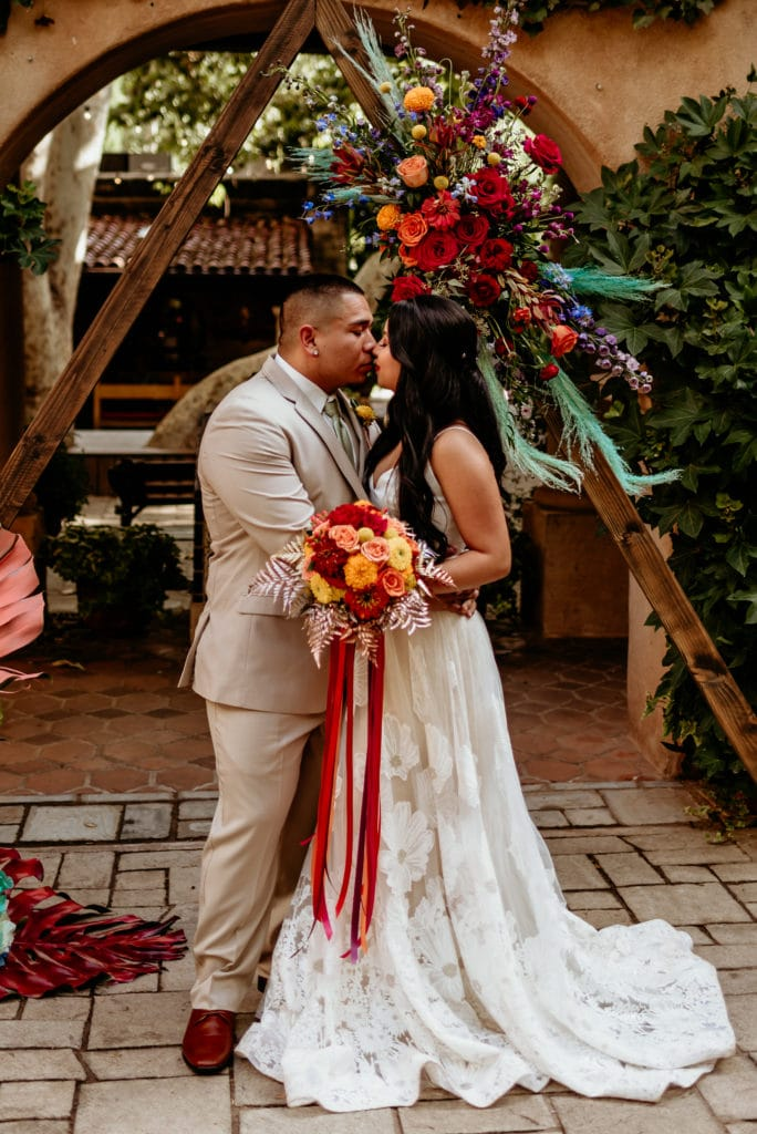 Couple kissing in front of wedding arch at Tlaquepaque