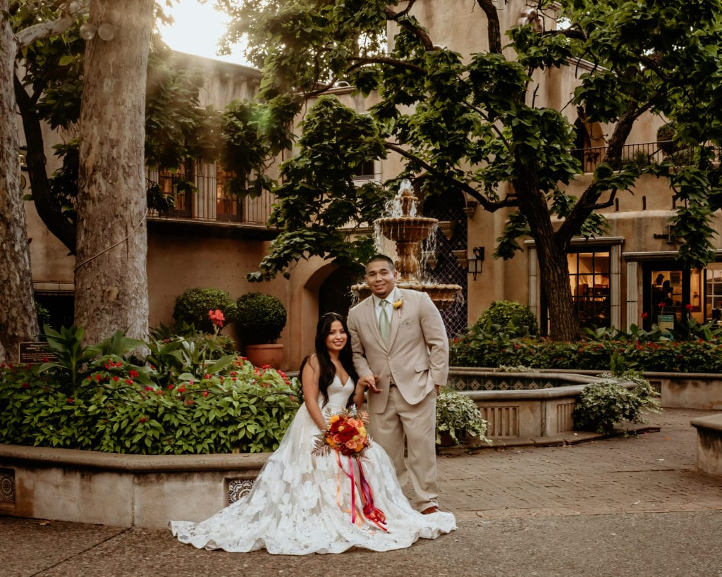 Bride and groom in front of courtyard fountain and trees