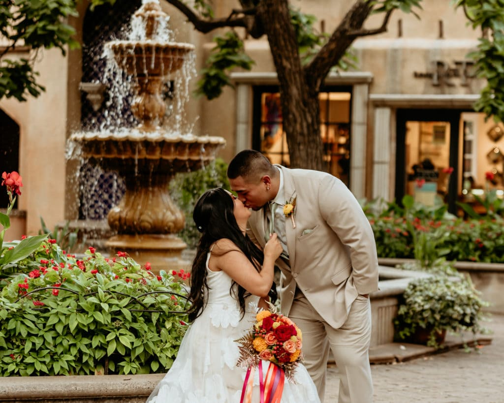 Bride pulling her groom down for a kiss in the Tlaquepaque courtyard in front of the fountain