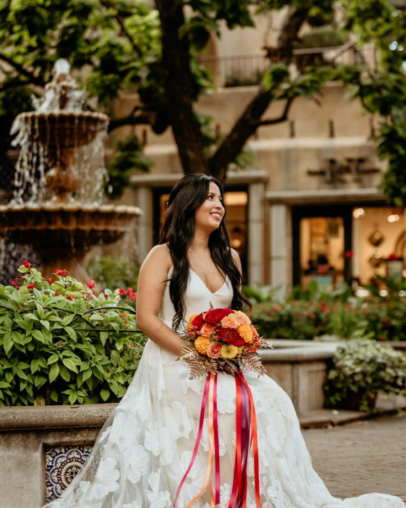 Bride in long flowered lace gown in front of courtyard fountin