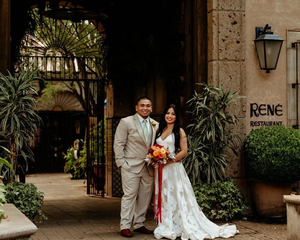 Old world stone walls and lush greenery surround bride and groom at Tlaquepaque