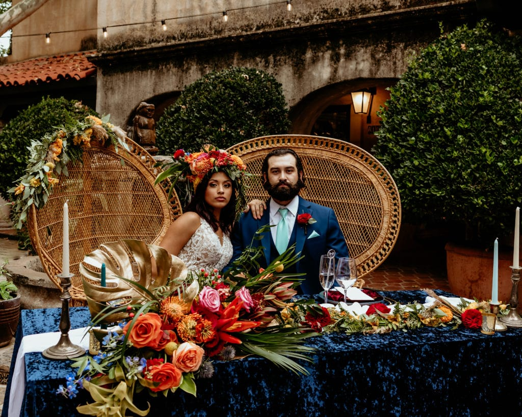 Bride and groom looking stoic and regal in wicker peacock chairs with tropical headdress and vibrant florals during their Tlaquepaque wedding